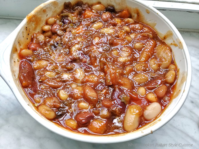 this is a slow cooked recipe in a big white bowl of barbecued cowboy style beans using 15 kinds of beans