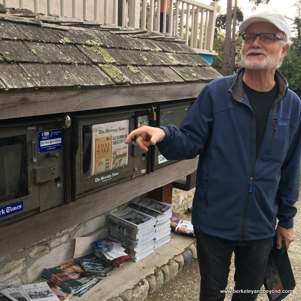 Carmel Walks guide Kelly Steele in front of rustic newstand in Carmel, California