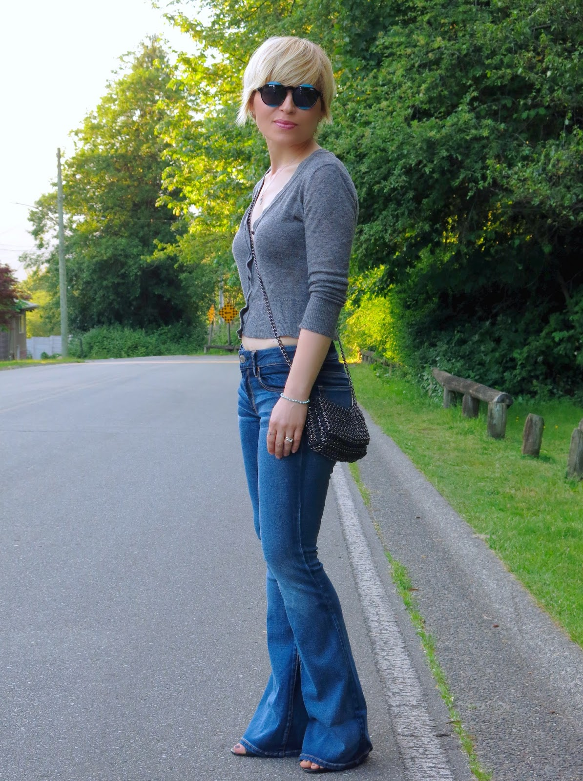 styling flare jeans with a cropped cardigan, cross-body bag, and statement sunglasses