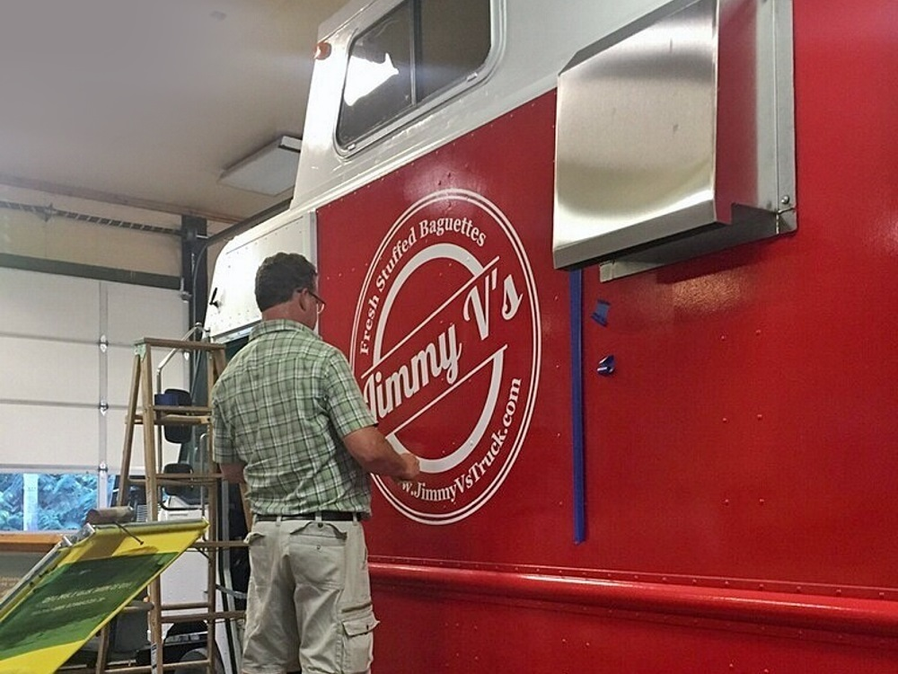Tom of New SIgns and Wonders installs Jimmy Vs Vehicle Graphic Logo