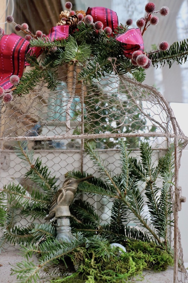 Christmas red plaid berry birdcage uses fresh tree clippings as background for a repurposed leaky bird faucet