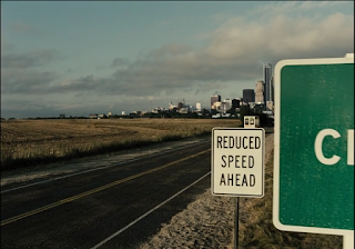 """Shot of the highway heading into Central City. A road sign says """"REDUCED SPEED AHEAD."""""""