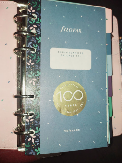 Inrerior of a ring bound planner, pink lining blue fly leaf, the gold sticker and put it on the fly leaf