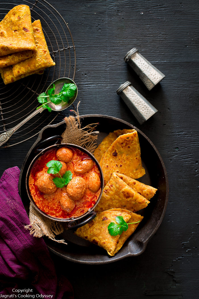Spicy orange colour baby potato curry served in cast iron bowl with indian flat breads.