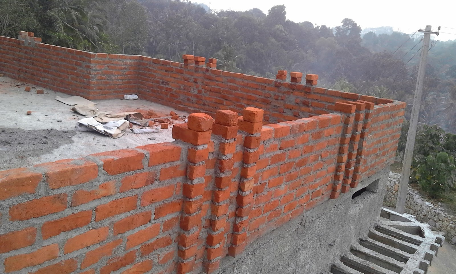 The parapet in the front portion has done with clay bricks ishtika here a pillar like structure which looks similar to pergola has created