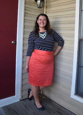 an outfit with a navy stripe tee, a mint necklace, a coral pencil skirt, and navy flats
