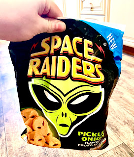 A big black bag containing light golden brown alien shaped potato shapes with a green alien logo on and space invaders pickled onion potato shapes in green font on a bright background