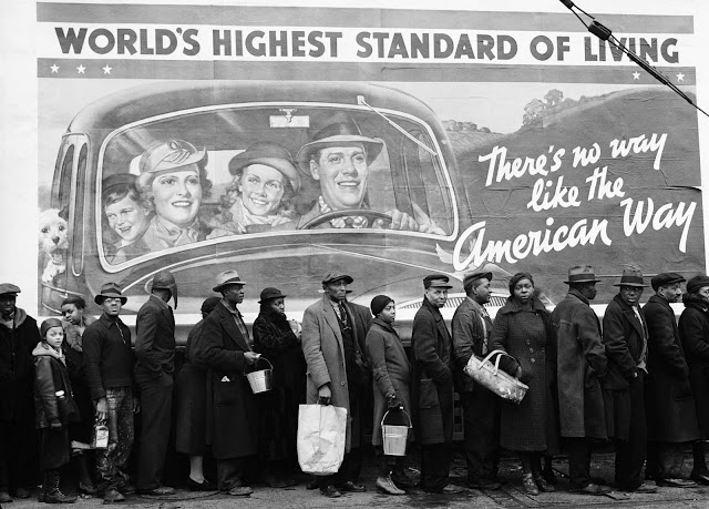 "Famous image of African American flood victims lined up to get food and clothing at Red Cross relief station in front of billboard ironically extolling ""World's highest standard of living. There's no way like the American way"". Original title of the picture: ""The Louisville Flood""."