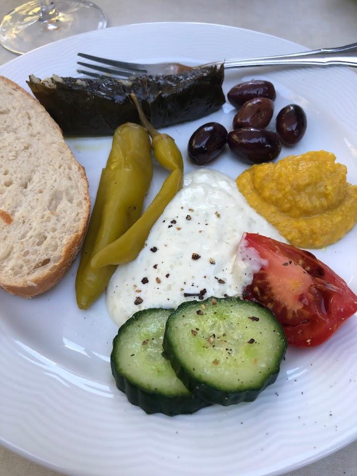Mediterrane Brotzeit mit Oliven, Tomaten, veganem Tsatsiki und hausgemachten Weinblättern (Dolmadakia)