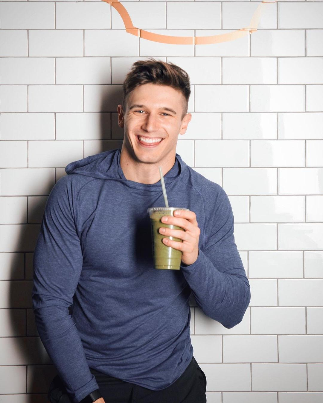 cute-fit-gay-guy-smiling-drinking-green-smoothie