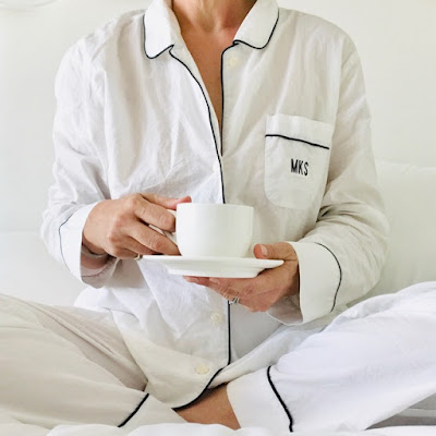woman sitting in bed wearing pajamas and holding a coffee cup and saucer
