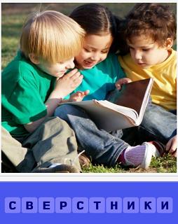 на траве сидят сверстники и читают вместе книгу