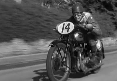Man riding racing motorcycle at speed.