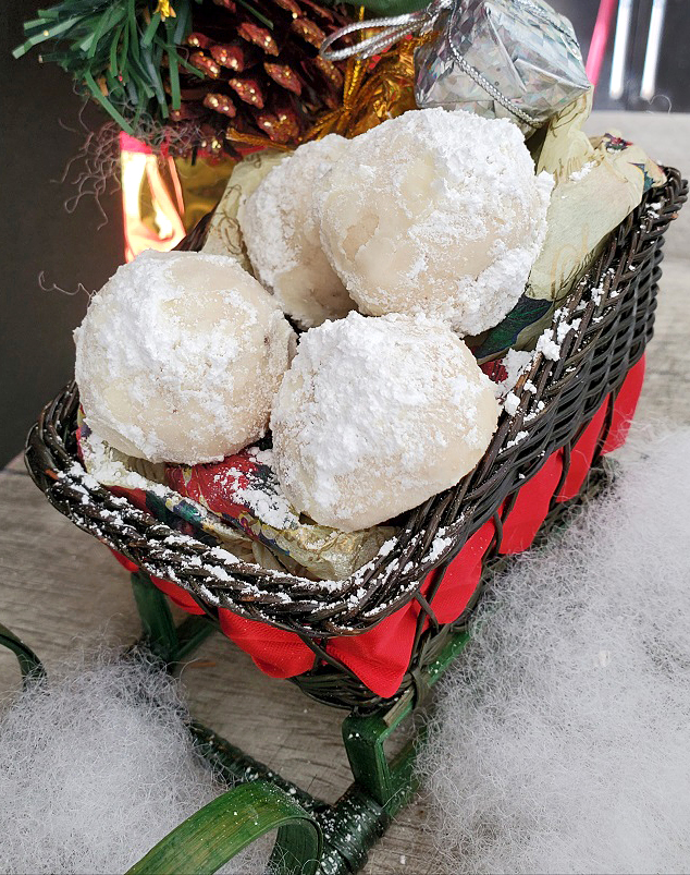 this is a Christmas sleigh full of butter cookies covered in powdered sugar that look like snowballs