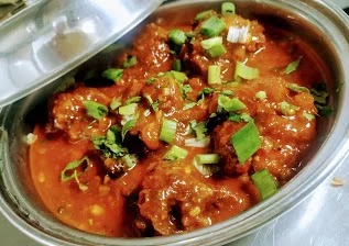 Serving chicken lollipop gravy in a bowl topped with spring onions
