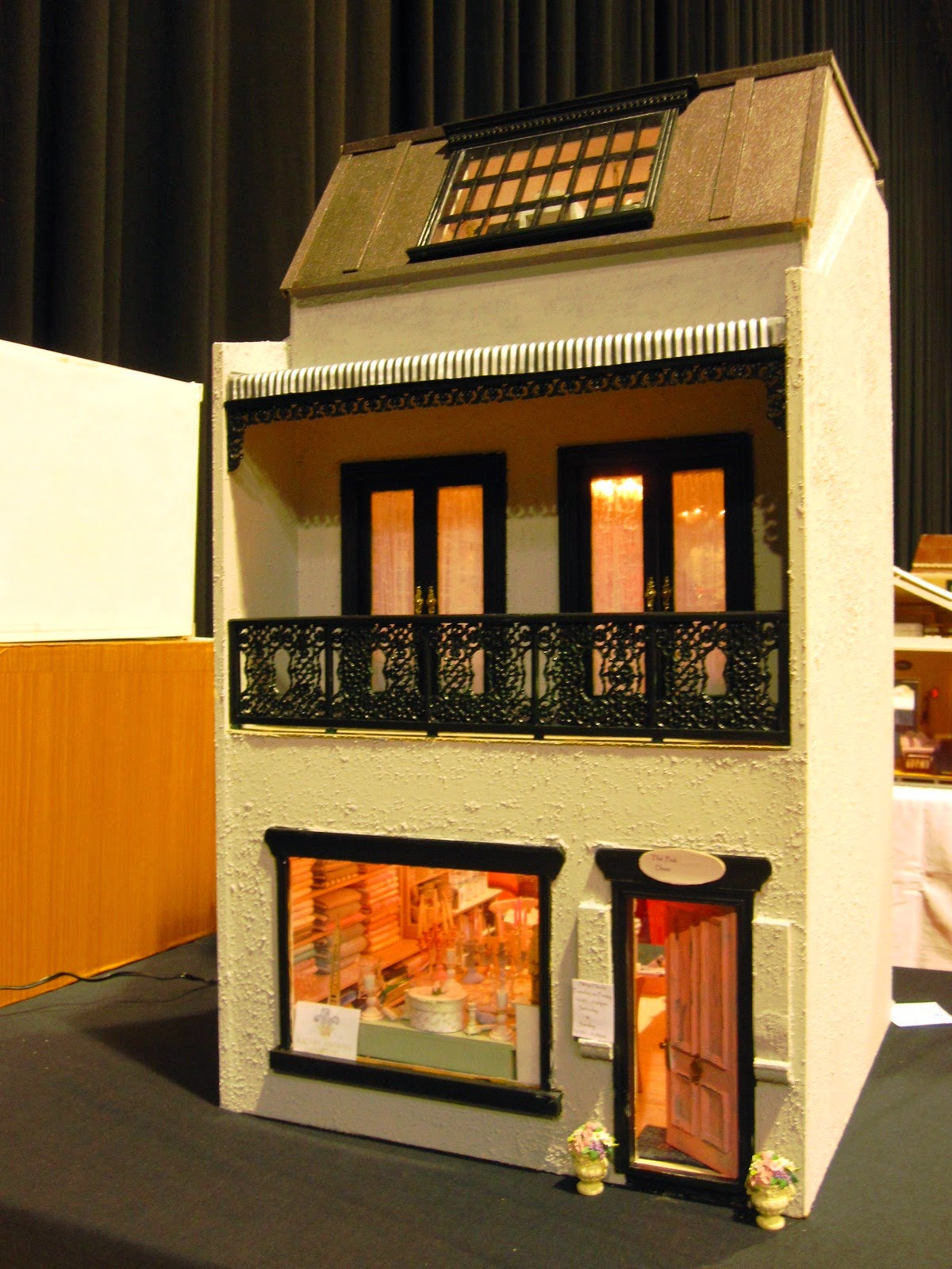Front view of a three-storey modern miniature shop building.