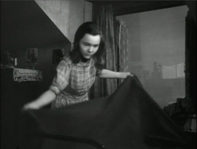 A hotel maid lifts a blanket into the air as she makes a bed.