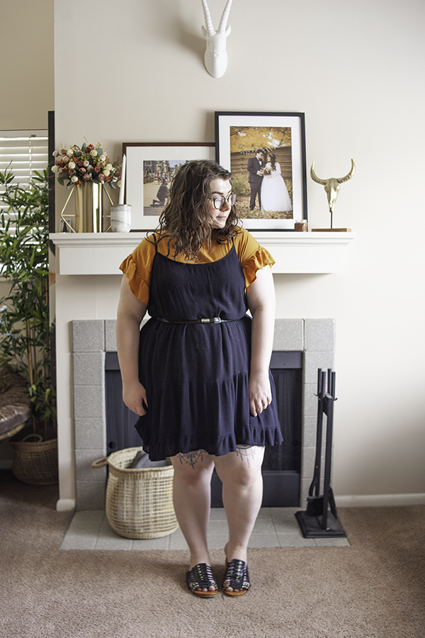 An outfit consisting of a yellow flounce short sleeve dress, black spaghetti strap dress over top, belted at the waist, with black caged open toe slide sandals.