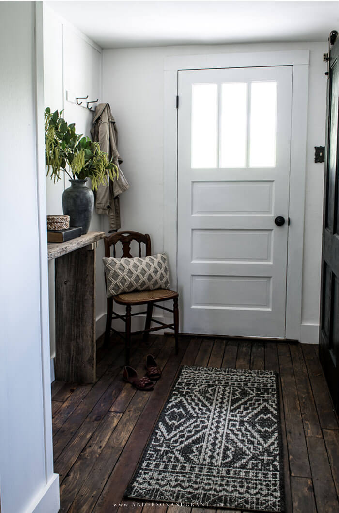 White entryway with black sliding barn door