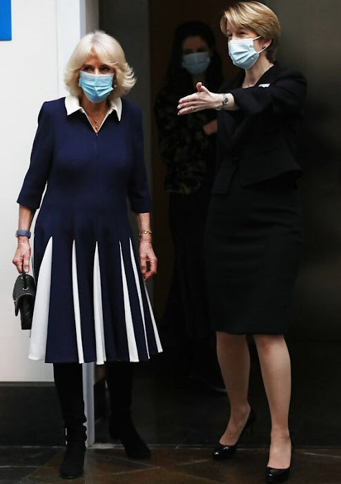 The Duchess wore a navy and white pleated and collar dress by Fiona Clare. Camilla paired it with black boots and Chanel handbag