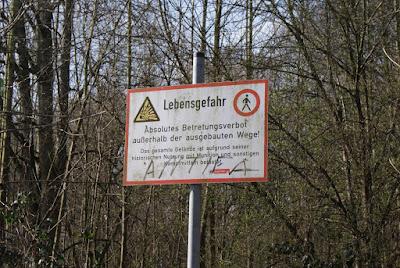 Eine Hinweistafel, die davor warnt, die Wege zu verlassen