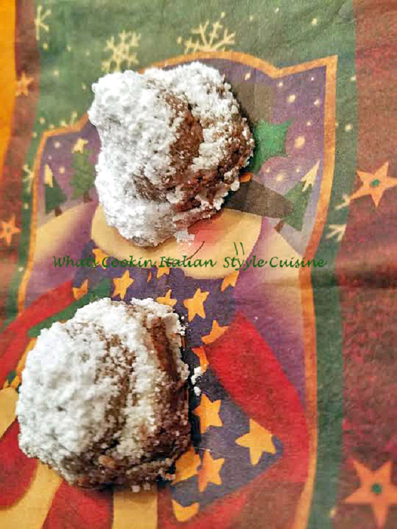 chocolate cookie dough wrapped around a hershey kiss rolled into powdered sugar. A chocolate lovers decadent dream cookie on a pretty star napkin for any Holiday treat