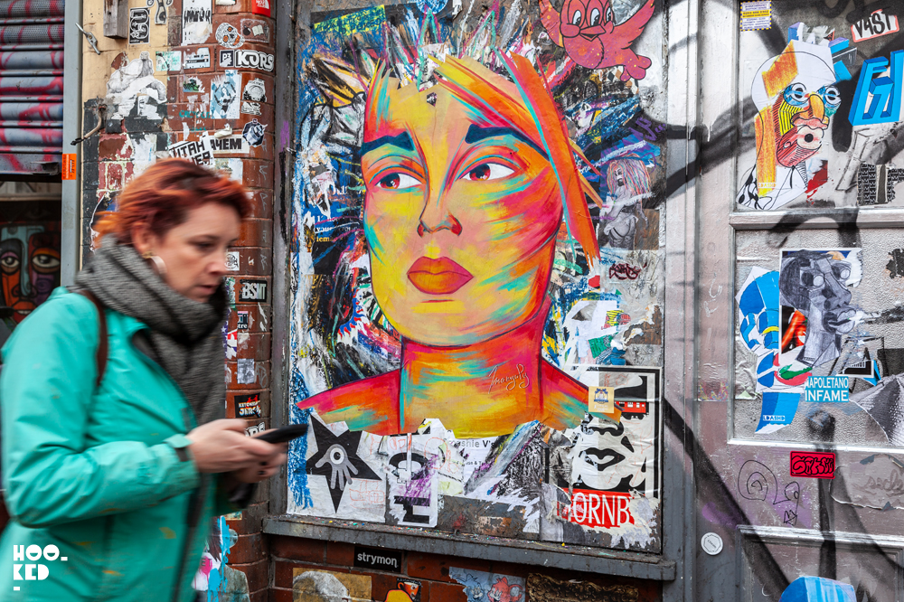 French Street Artist Manyoly in London with female portrait pasteups