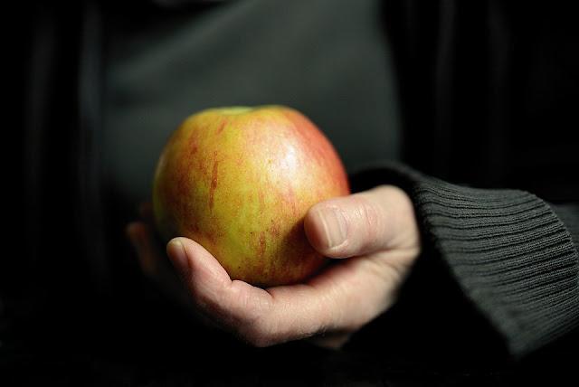 يد تحمل تفاحة