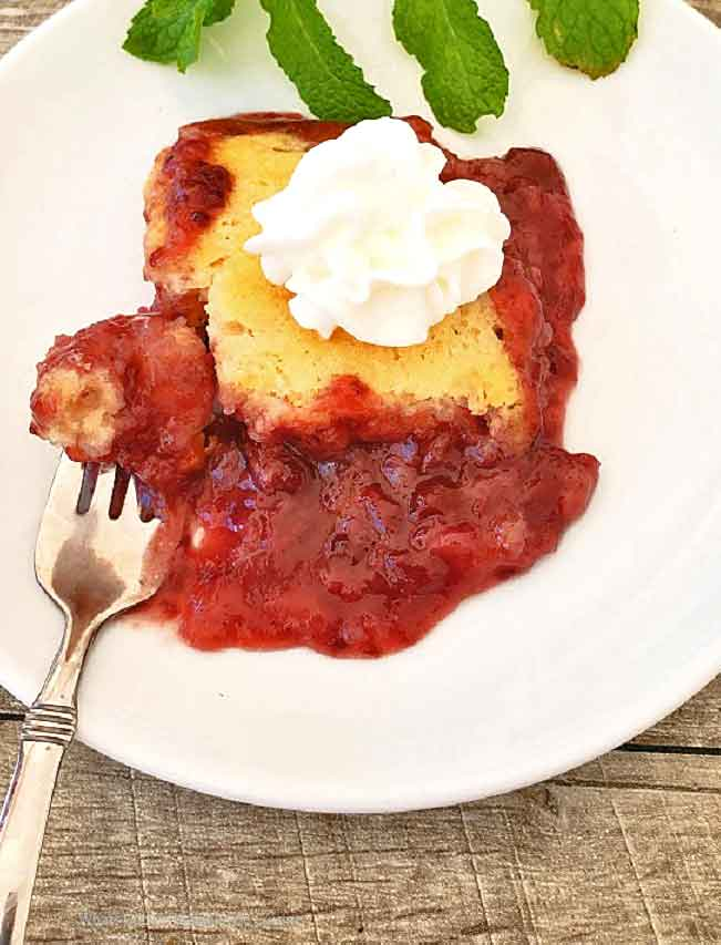 this is a red raspberry cobbler with a cake like topping on a white plate and gray board there is also a mint garnish and shiny fork on the plate