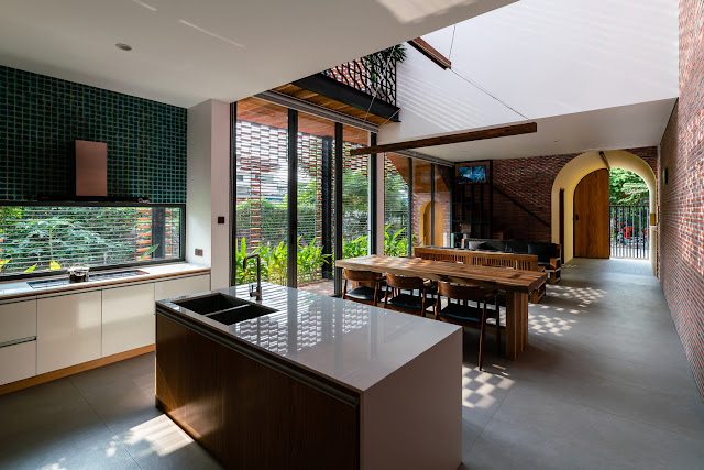 open floor plan with small square emerald green kitchen backsplash tiles, high windows that geometric grate that plays light onto brick walls, arch doorway