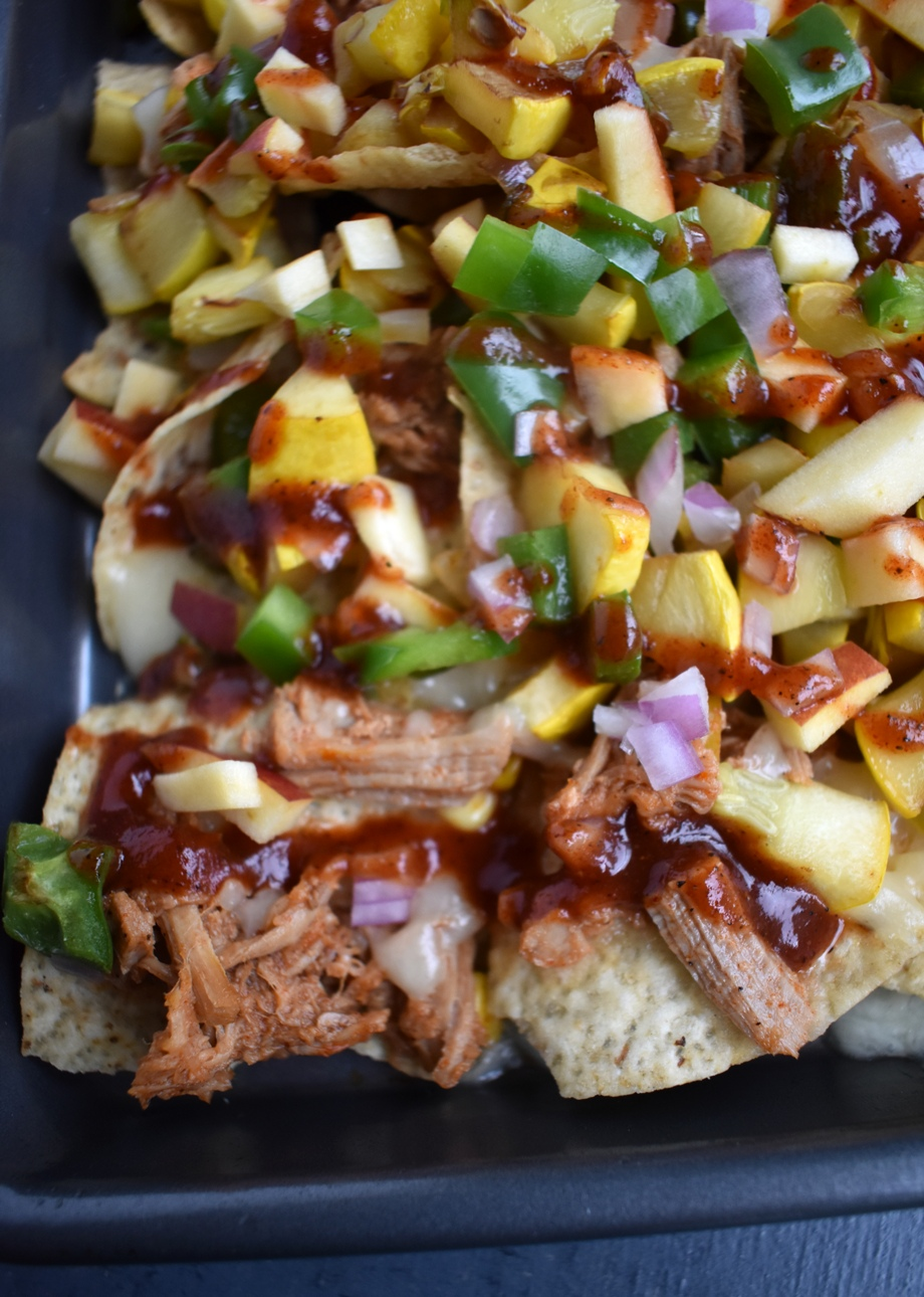 Loaded BBQ Pulled Pork Nachos are loaded with shredded pork, melted cheese, sauteed corn, bell peppers and onions and crunchy apples with a homemade drizzled smoky barbecue sauce! www.nutritionistreviews.com