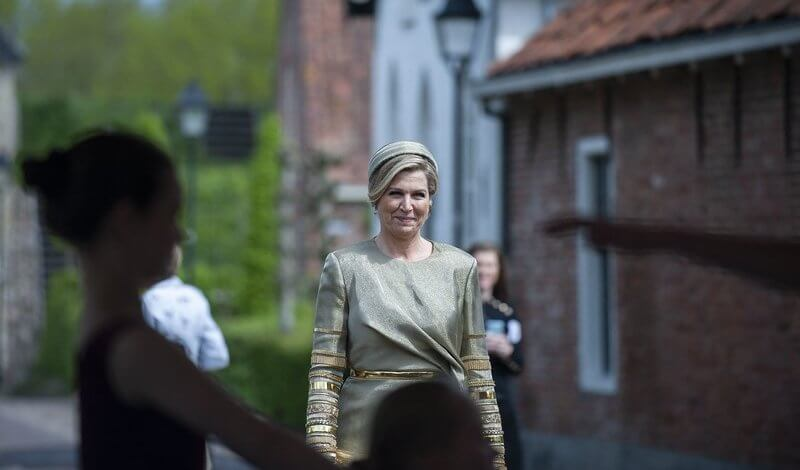 Queen Maxima wore an embellised draped midi dress by Claes Iversen. Gianvito Rossi gold plexi pumps. Begum Khan clutch bag