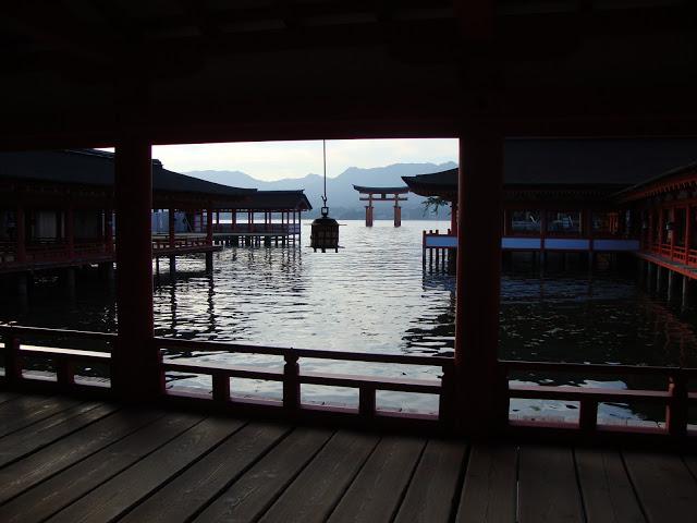 cala la sera nei corridoi del santuario con il torii sullo sfondo