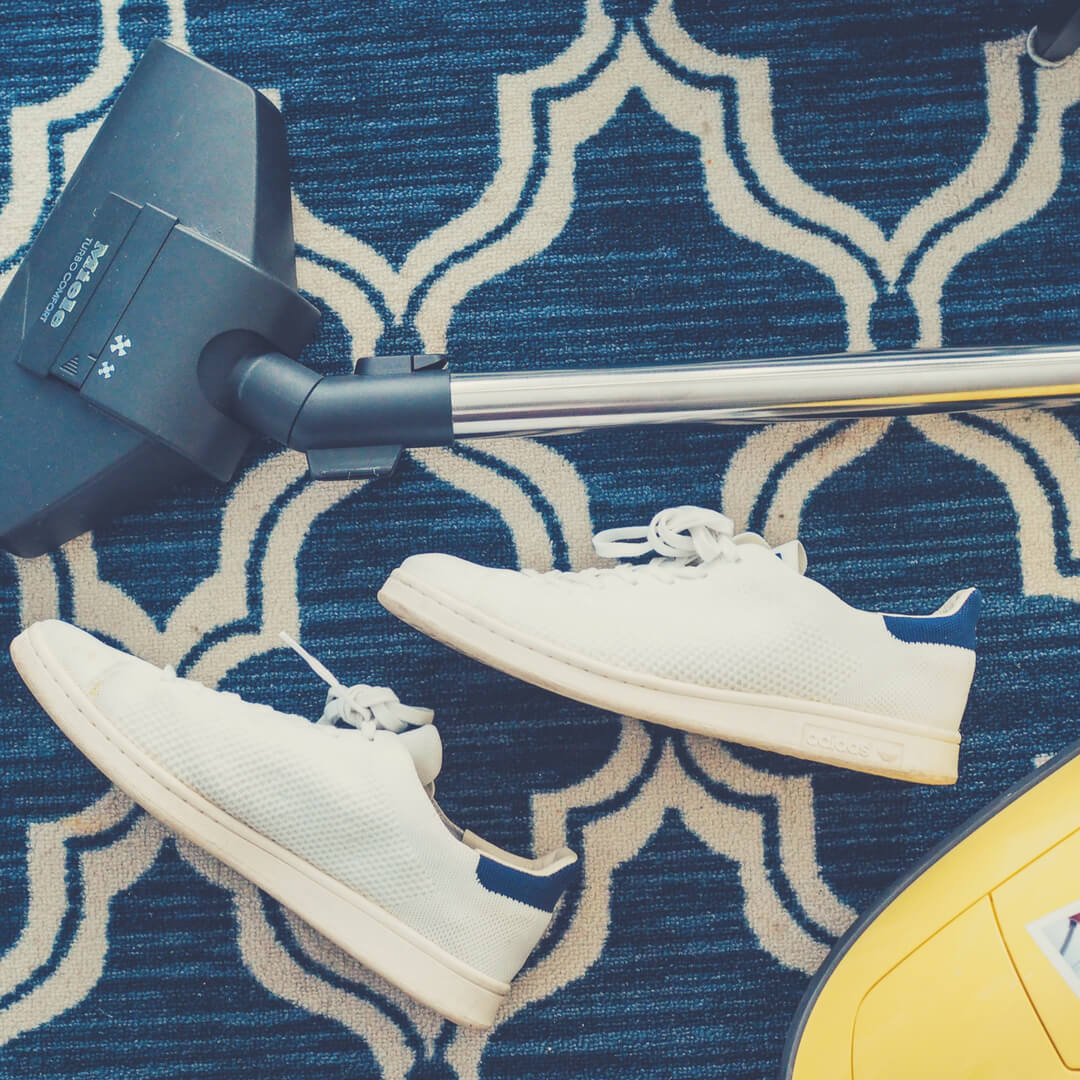 A vacuum cleaner sits on the carpet next to a white pair of trainers. A good, age-appropriate chores for your teens - vacuuming.