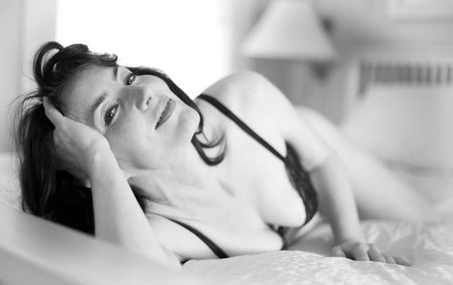Sexy middle-aged woman in lingerie, lying in bed