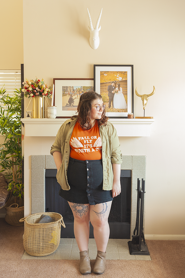 "An outfit consisting of an olive green jacket, orange graphic tee with the text ""Fall or Fly It's Worth A Try"" tucked into a black button down mini skirt and boots."