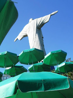 Christ the Redeemer from behind with outstretched arms and green umbrellas