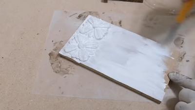 قطعة من عجينة الخشب يتم دهانها ببلاستيك مائي أبيض