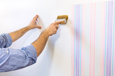 Pic of man's hands applying glue with brush for next sheet of wallpaper