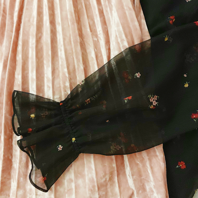 A flatlay of black semi sheer floral microprint dress layered over a pastel pink velvet midi skirt.
