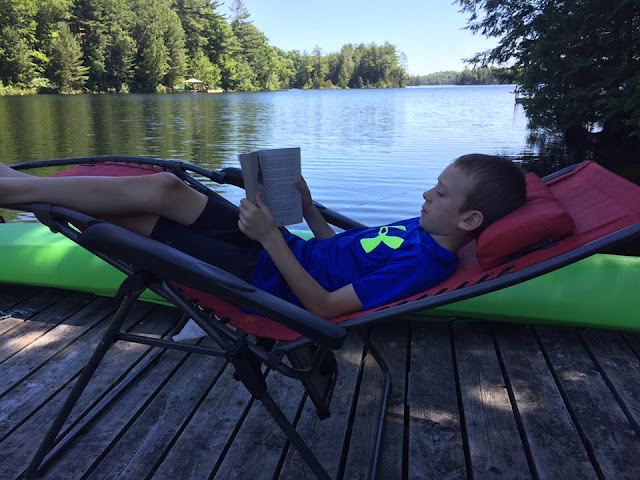boy reclining on a dock reading