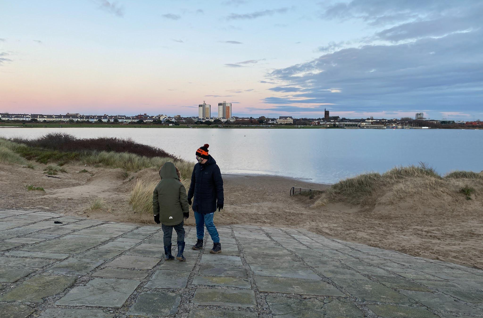 boy and dad waling by a marina