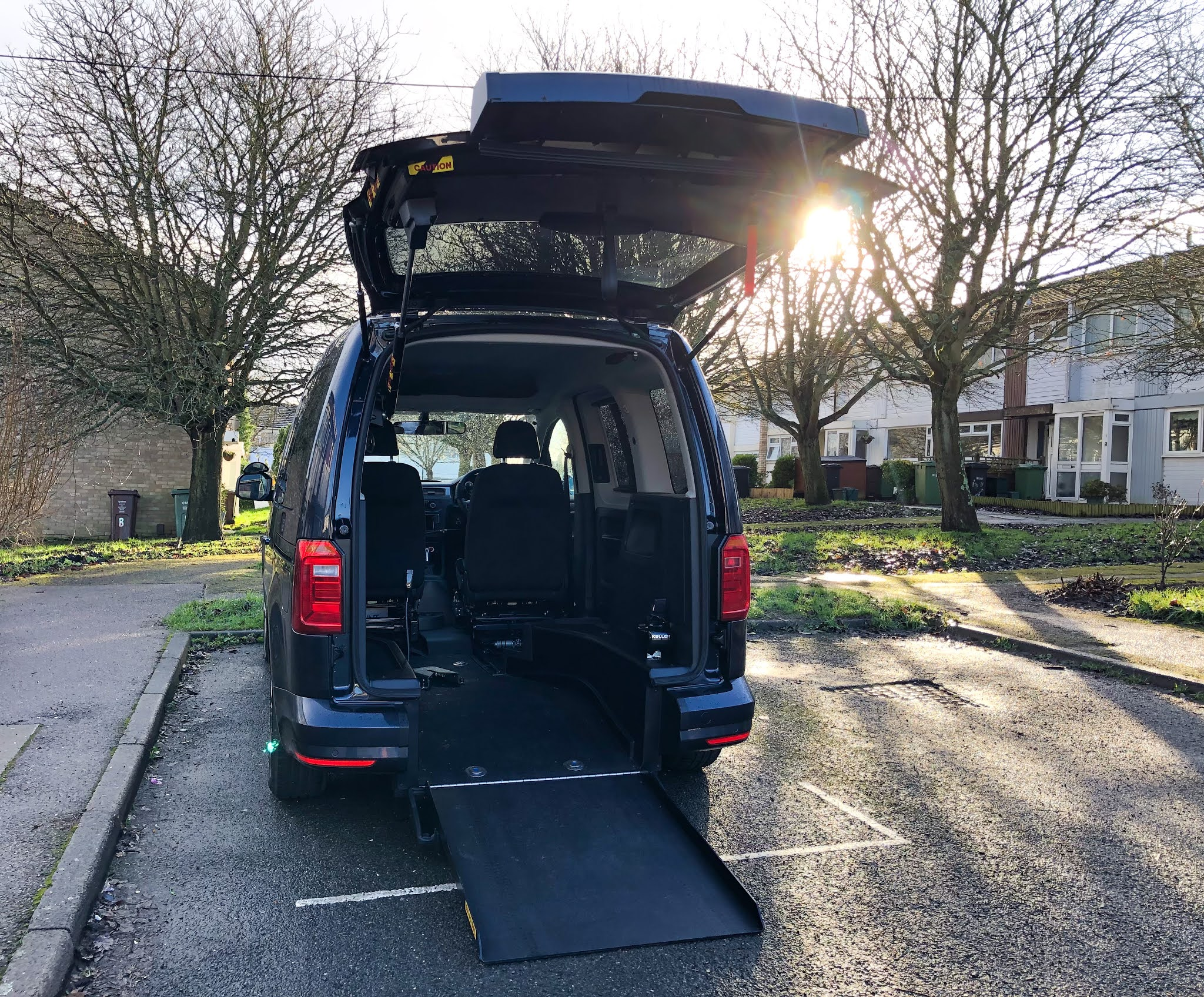 A midsize wheelchair accessible vehicle has it's boot opened and ramp extended.