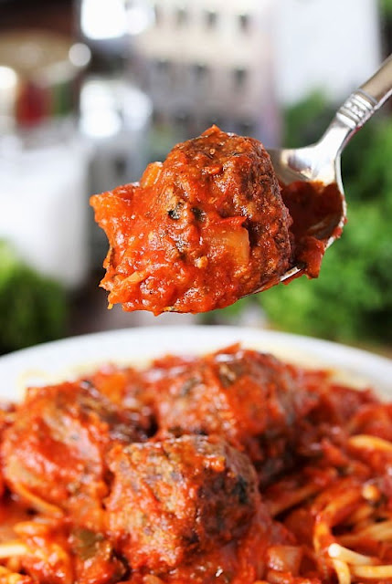 Spooning Meatballs Over a Plate of Homemade Spaghetti and Meatballs Image