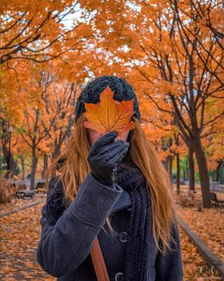 foto tumblr tapándose la cara con una hoja en otoño