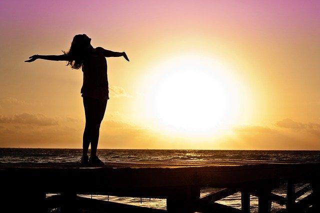 Wanita yang sedang menikmati indahnya sinaran matahari