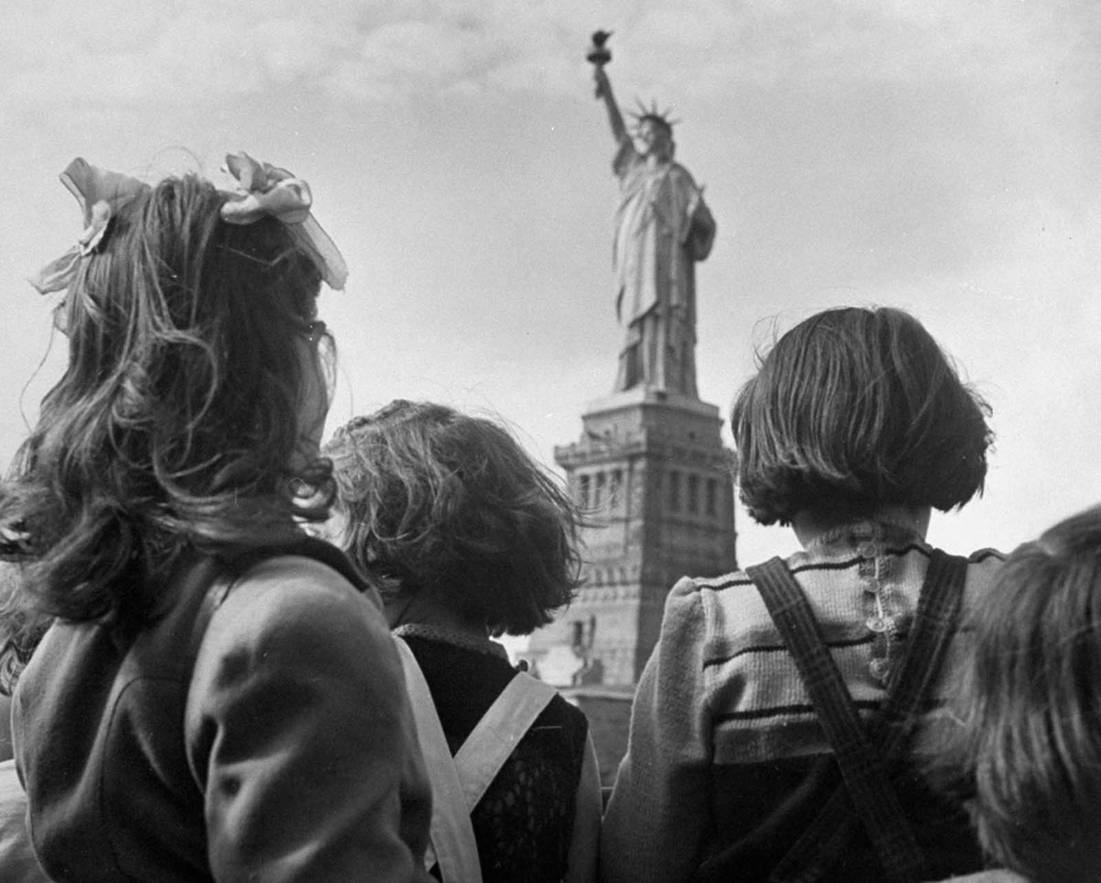 In 1946, refugee children gaze at the Statue of Liberty from the railing of a boat.