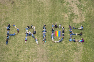 Students laying on Green spelling out PRIDE