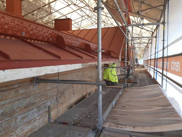 Työmies korjaa rakennusta, joka on ympäröity työmaatelineillä.