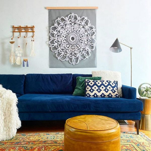 quilled round paper doily hanging on wall over couch